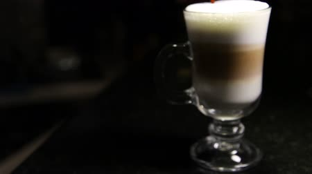 drinking coffee : A jet of coffee is poured into a glass of mochaccino or latte.Blurred background.Copy space