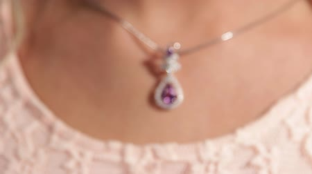 drahokamy : Jewellery.A silver pendant with a magenta diamond on the pretty girls neck.Shallow depth of field