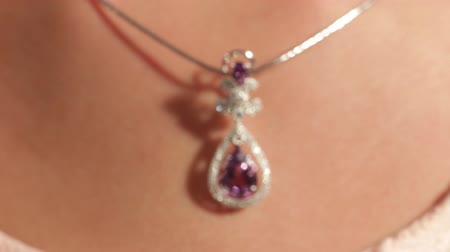 кулон : Closeup of silver pendant with a magenta diamond on the pretty girls neck.Jewellery.Shallow depth of field Стоковые видеозаписи