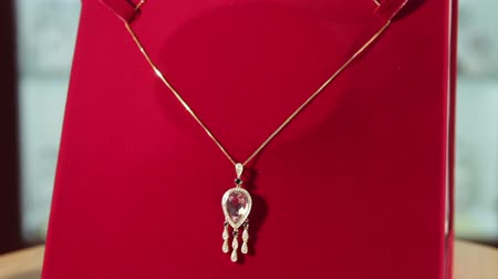 кулон : Silver pendant with magenta diamond rotates on a red velvet stand in the jewelry store.Jewellery