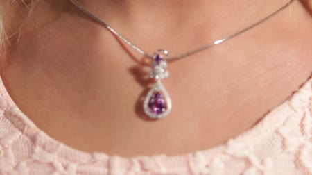 кулон : Beautiful female neck, on it is a silver pendant with a magenta diamond.Jewellery.Shallow depth of field