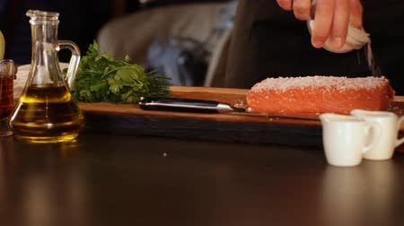 augurk : The cook sprinkles with coarse salt a large piece of raw salmon fillet. Fast pickle. High protein foods Stockvideo