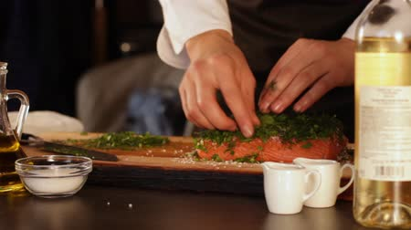 filet : The cook sprinkles finely chopped herbs with a large piece of raw salmon fillet. Quick marinade. High protein foods Stock Footage