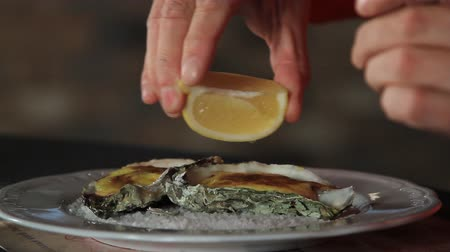 oysters : A man pours oysters with lemon juice cooked with hollandaise sauce. Dutch sauce