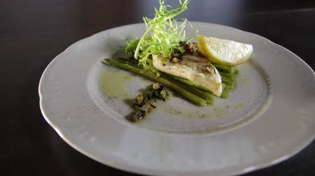 zander : Grilled zander fillet with asparagus and lemon.White plate