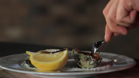 oysters : The process of eating oysters cooked with Dutch sauce. Hollandaise sauce