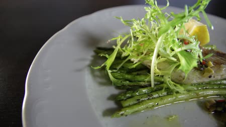 szczupak : Blanched asparagus and grilled fillet of pike perch, served with lemon and herbs on a white plate