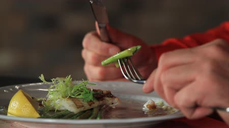 zander : A man eats blanched asparagus and grilled fillet of pike perch, served with lemon and herbs.close-up