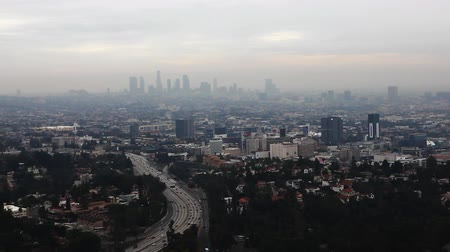 ködös : A twilight view of the Los Angeles City Center with a busy expressway in the foreground Stock mozgókép