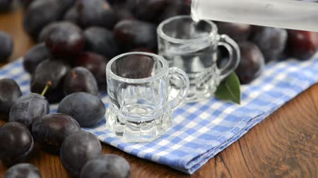 hz : pouring plum liquor in two short glasses on white blue dish towel Stock Footage
