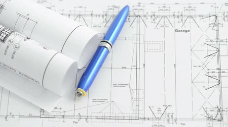 прокатка : A pen rolls over  an architectural drawing blueprint. Two sequences in one video. Стоковые видеозаписи