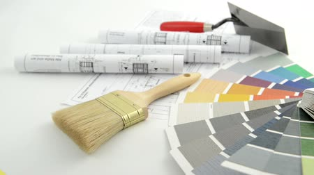 vonalvezetés : Architectural drawing blueprint. In background a trowel brush  and color swatch for painting. Racking focus Stock mozgókép