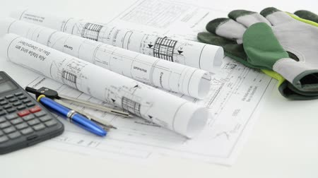 architektonický : Pricing an architectural drawing blueprint with calculator pen and working gloves. Racking focus