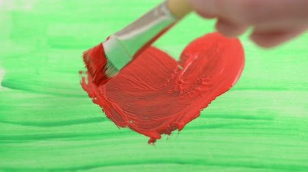 canvas : Painting a red heart on green background with water color and paintbrush