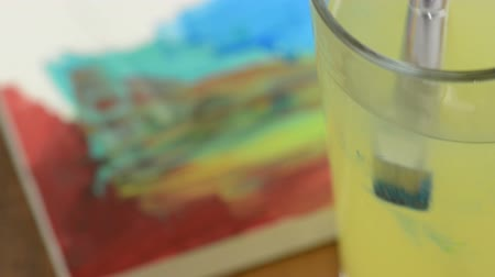 akvarell : Cleaning a brush with blue water color in a water glass