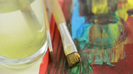 чистый : Cleaning a brush with yellow water color in a water glass