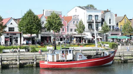 hanseatic : Warnemuende, Germany - August 13, 2014: People visiting harbor with boats and stores. Stock Footage