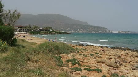 malia : Stalis, Crete  GREECE May 16 2017: Landscape on the beach at Stalis at Malia on Crete (Greece). People enjoying the beach. Rocks in water. bars and restaurants in background.