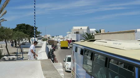 УВР : Ia, Santorini  GREECE May 15 2017: Cityscape of Ia, Santorini Isle (Greece). Buses passing by a small road. Traffic jam.