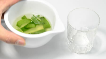 вера : Aloe vera pieces on a turn table and pouring Aloe vera juice into a glass