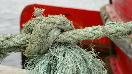 knotted : Swinging mooring line of a trawler with a big knot