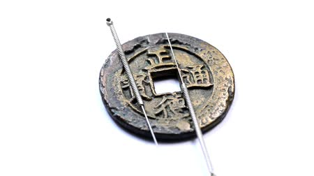 felsefe : acupuncture needles on chinese coins on a turn table