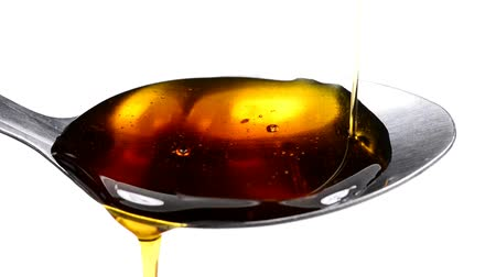 adoçante : Maple syrup running down on a spoon