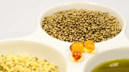 unpeeled : Hemp seeds, unpeeled, peeled, hemp oil capsules and hemp oil on a turn table Stock Footage