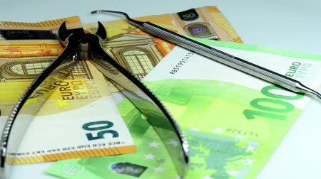 alicate : Dental forceps with euro bills Stock Footage
