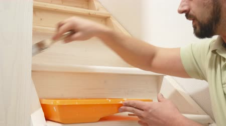 decorador : man paints a wooden ladder with a brush in white