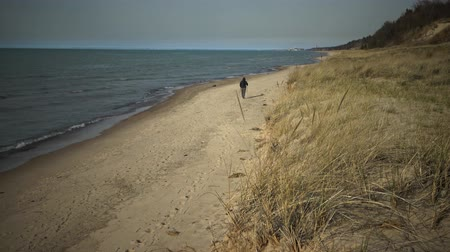 sicília : A pedestrian walks along the shore of the lake along the sand dunes Stock Footage