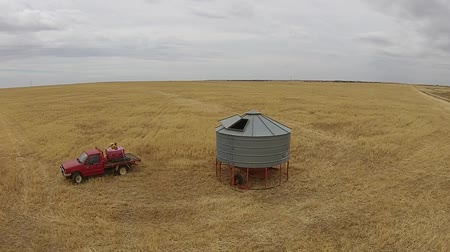 slashing : Aerial footage of farmer with silo getting ready to harvest crop