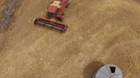 slashing : Overhead Aerial footage of crop harvester, filling silo and harvesting hay paddock in rows, around huge paddock in drought stricken dry land farming area of Australia and filling grain silo read for stock piling Stock Footage