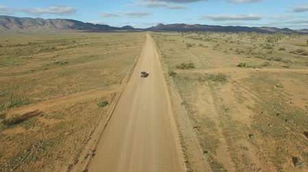 řídit : Elevated aerial view video footage of vehicle car traveling off-road on outback rural Australian dusty dirt road or track. Driving open road sense of freedom to horizon vista for holiday travel, camping, four wheel drive 4wd themes or getting lost in the