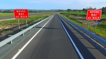 yolları : Wrong way go back road signage on major high speed highway freeway motorway exit or off ramp turning. Life journey bad choices Stok Video