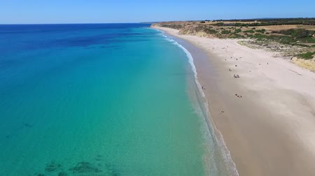 copter : Helicopter aerial view of calm sandy bay Port Willunga with old shipping jetty  fishermen beach caves near Aldinga Beach in South Australia on Fleurieu Peninsula. Spectacular coastline cliffs and reef. Stock Footage
