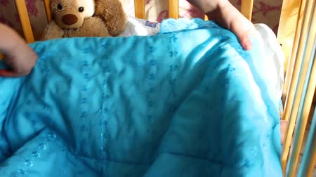 cobertor : sleeping baby covered with a blanket in the crib