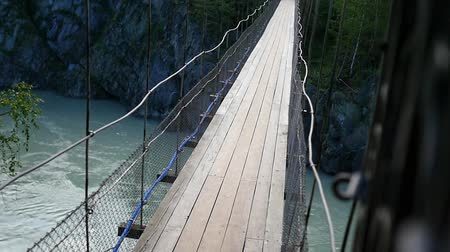 подвесной : people crossing suspension bridge