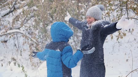 queda de neve : girl and child throwing snow over himself and enjoys it in the winter park Vídeos