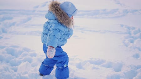 deep snow : the child walks in deep snow drifts in the park