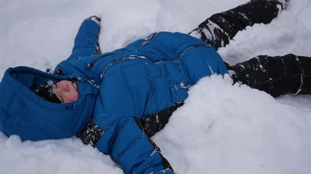 snow angel : child making a snow angel in slowmotion