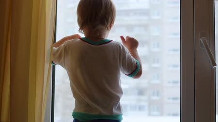 side window : a child stands on the windowsill and looking out the window Stock Footage