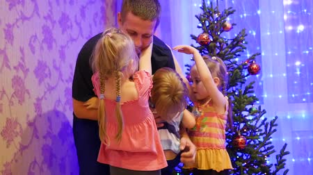 отцовство : Happy father holds on the hands of children, smiling and laughing in a Christmas evening. In the background, lights and garlands of Christmas fir