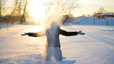 парк : a girl throws snow above head on sunset background