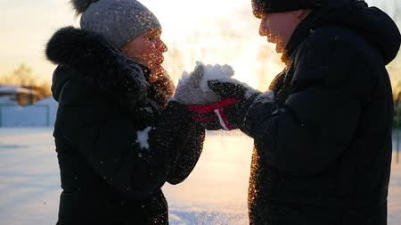 иней : girl and guy blows snow with hands on sunset background