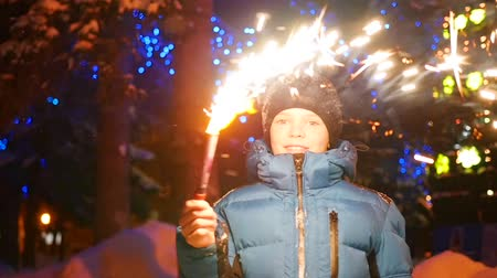 to celebrate : The child holds the firework outdoors in the winter. Slowmotion . In the background, lights and garlands of Christmas fir
