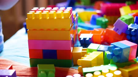 oynamak : A young child plays in the constructor. Game of the childrens designer. Colored cubes.