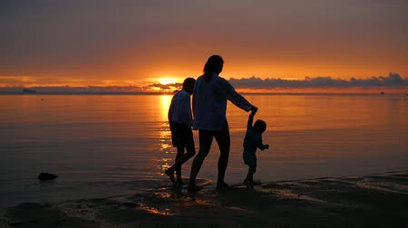 irreconhecível : the girl with the children go for walks and play on the beach at sunset time