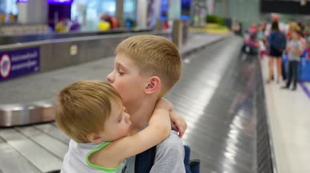 reclaim : Children stand in the baggage claim area at the airport Stock Footage