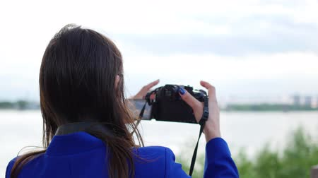 make photo : young girl doing a video on the camera. To pose for the camera. Fun outdoors Stock Footage